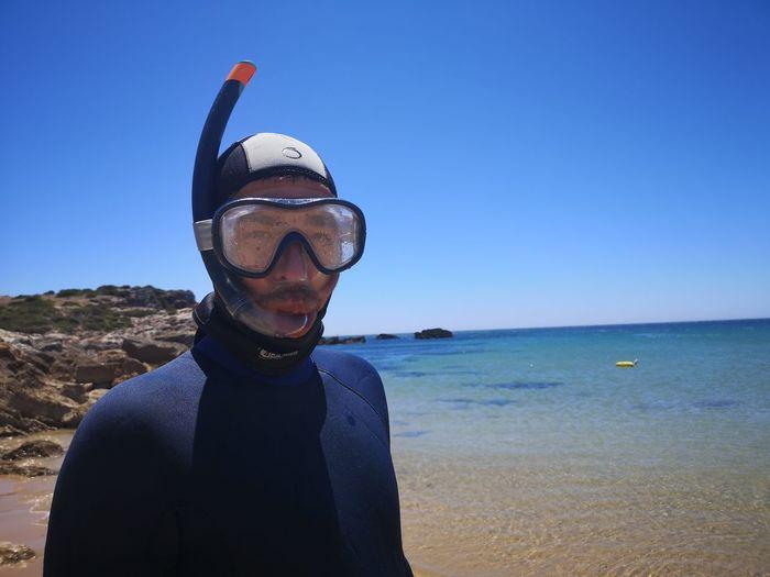 Portrait of man on beach against clear blue sky