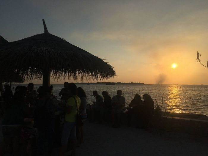 Real People Silhouette Sunset Sky Sea Tranquil Scene Scenics Nature Beauty In Nature Tranquility Water Women Lifestyles Thatched Roof Leisure Activity Outdoors Large Group Of People Friendship Beach Picnic Maldives Male Rasfannu Maafannu Flyboard Miles Away