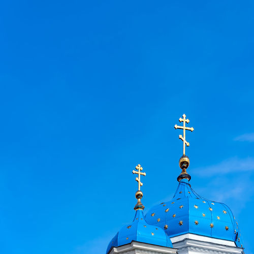 Christian Orthodox Church Cupolas with blue roofs, golden stars and golden crosses on top, against a blue sky of the same color Orthodox Church Russia Architecture Belief Blue Building Christian Orthodox Cross Clear Sky Copy Space Cupola Guidance Low Angle View No People Place Of Worship Religion Russian Architecture Sky Spirituality