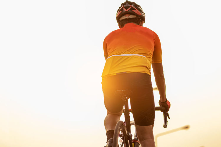 Rear view of man riding bicycle against sky during sunset