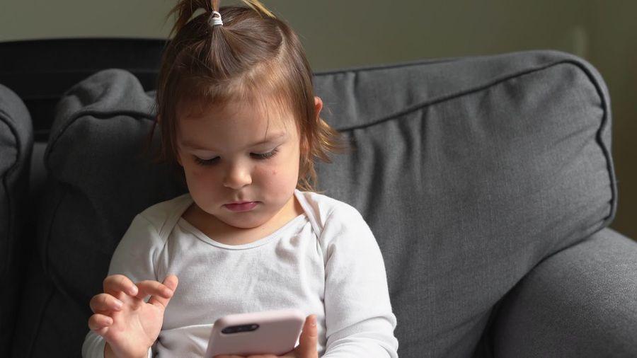 Full length of girl using mobile phone while sitting on sofa