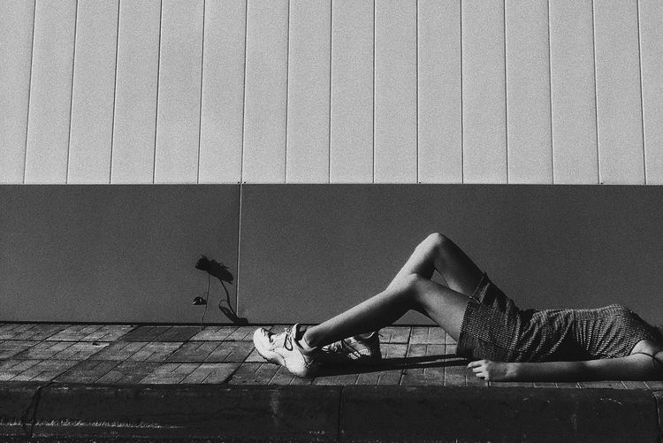 Side view of woman lying on wall