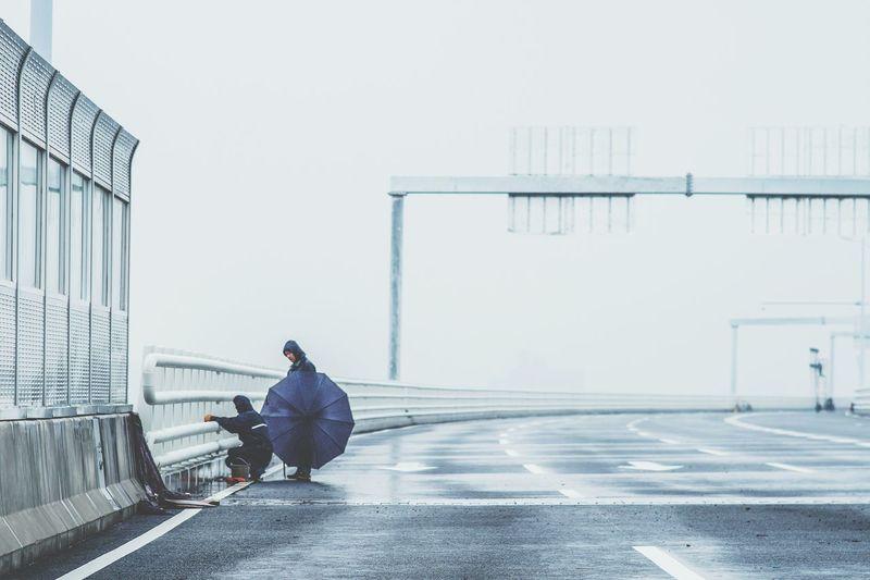 Manual Workers Cleaning Bridge Railing Against Sky