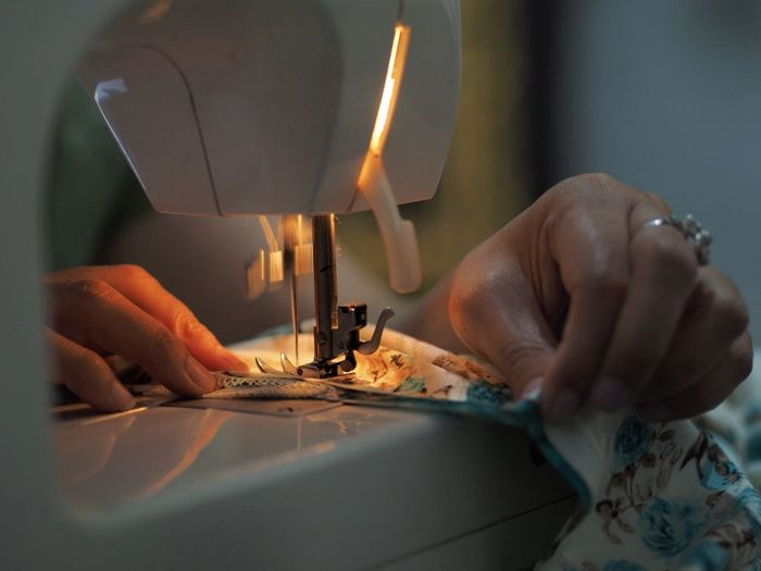 Close-up of woman stitching clothe on sewing machine