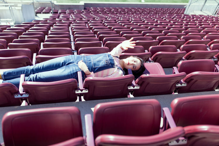 High angle view of girl lying down on seats in stadium