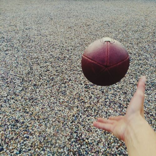 Cropped image of person playing america football on beach