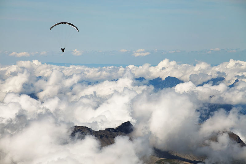 Person paragliding over cloudscape against blue sky at swiss alps