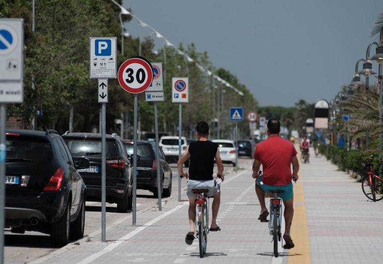 Rear view of man riding bicycle on road in city