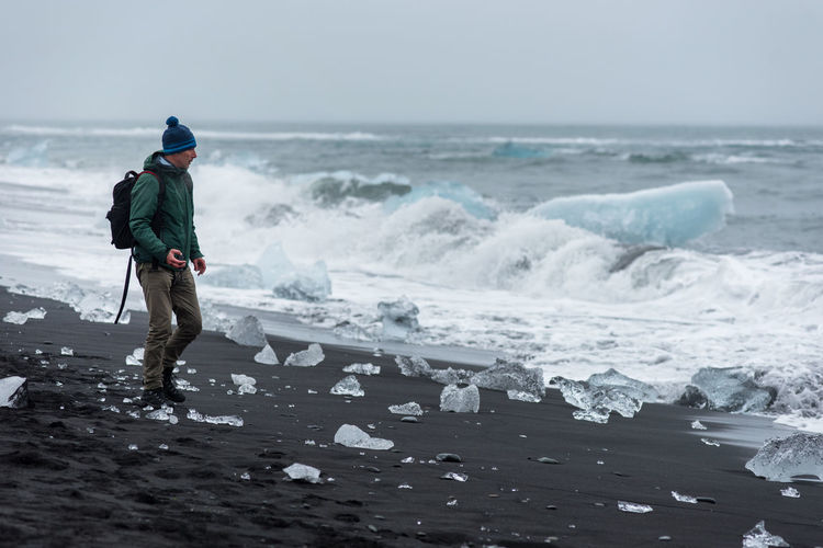 Man standing at beach during winter