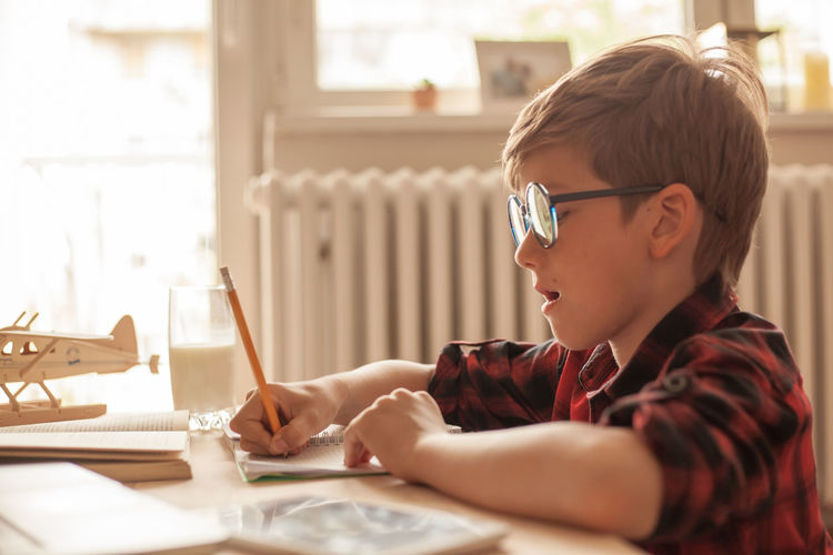 Nerdy elementary student writing his homework in the living room.