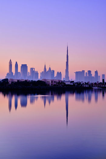 Reflection of buildings in city at sunrise