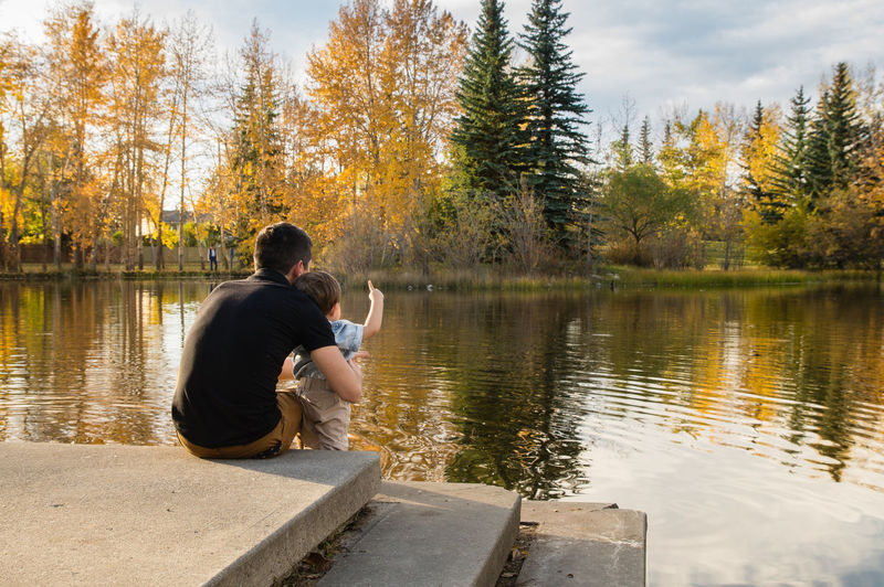 Father and son enjoying view of lake