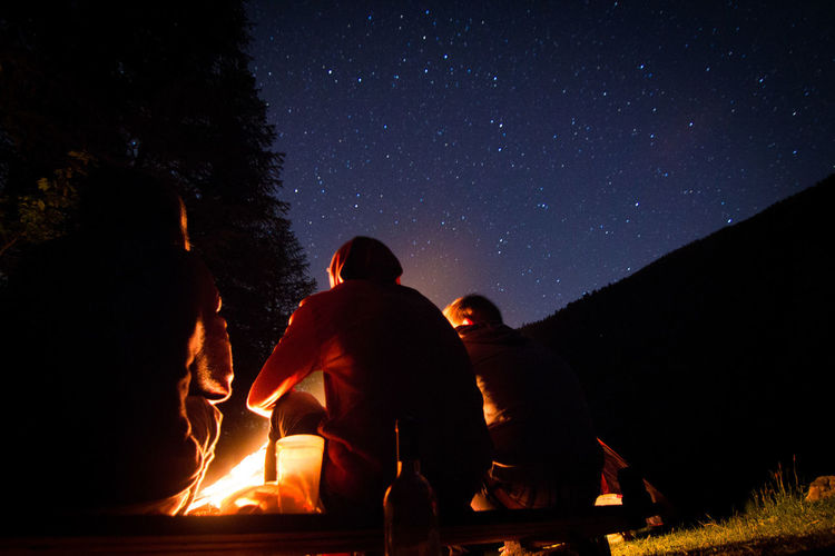 Rear View Of Friends Sitting By Campfire Against Star Field