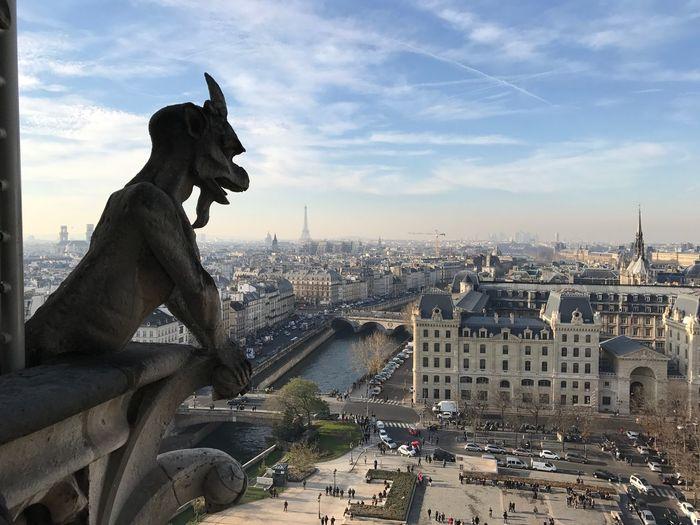 Close-Up Of Gargoyle Statue Against Cityscape