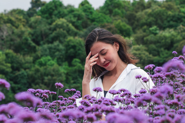 Portrait of woman on purple flowering plants