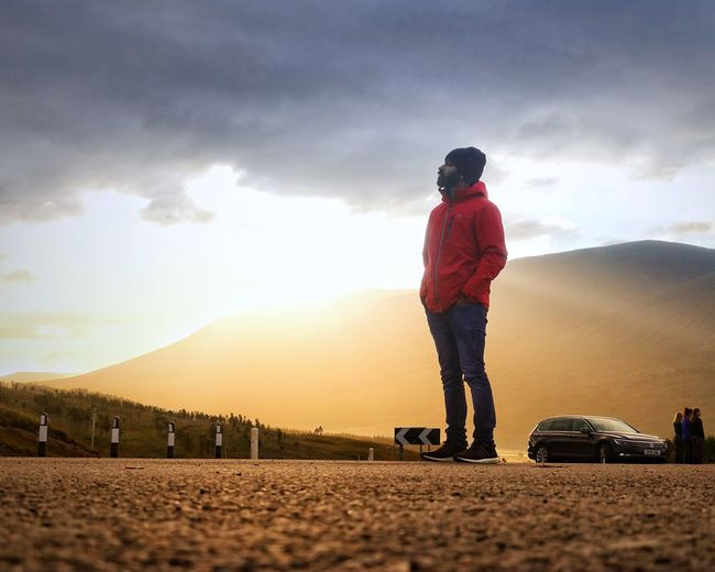 Rear view of man standing on road against sky during sunset