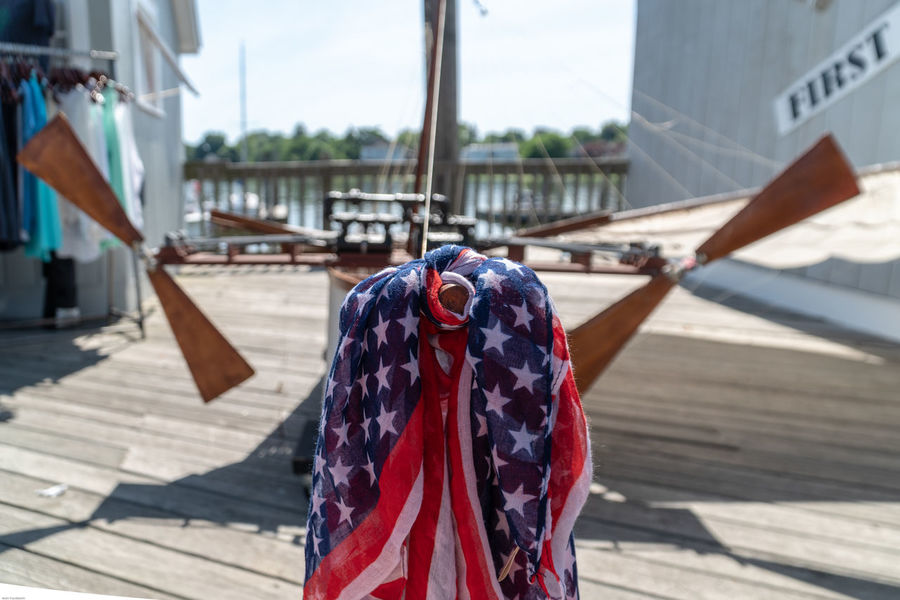 Pier Architecture Boardwalk Built Structure Close-up Clothing Day Flag Flight Focus On Foreground Hanging Nature One Person Outdoors Patriotism Real People Selective Focus Sunlight Sunny Textile Transportation