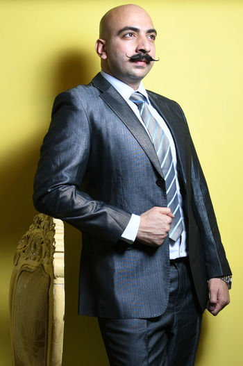 Businessman standing against yellow background