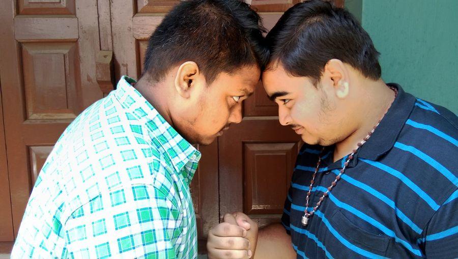 Close-up of friends standing against door