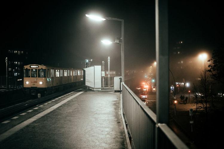 Illuminated street lights in city against sky at night