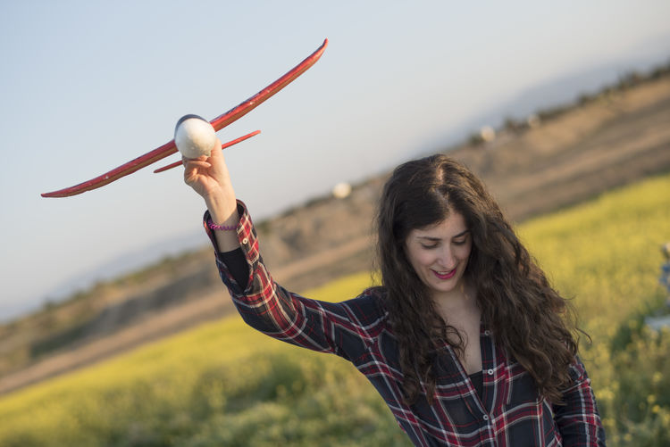 Smiling woman holding model airplane while standing on land
