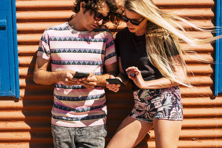 Man and woman using mobile phone against wall