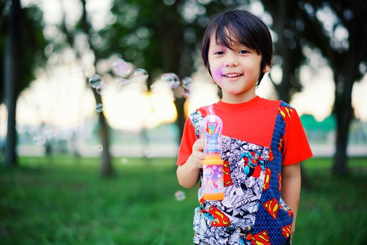 Portrait Of Smiling Boy With Toy On Field