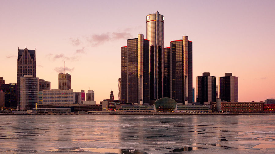 Modern Buildings By Frozen Lake In City During Sunset
