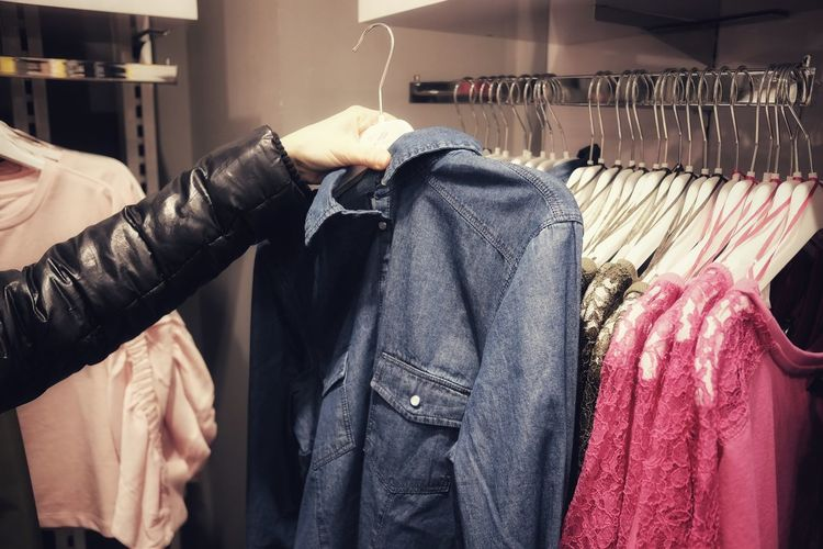 Close-Up Of Woman Buying Clothes At Shop