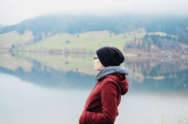 Woman looking away standing against lake during winter