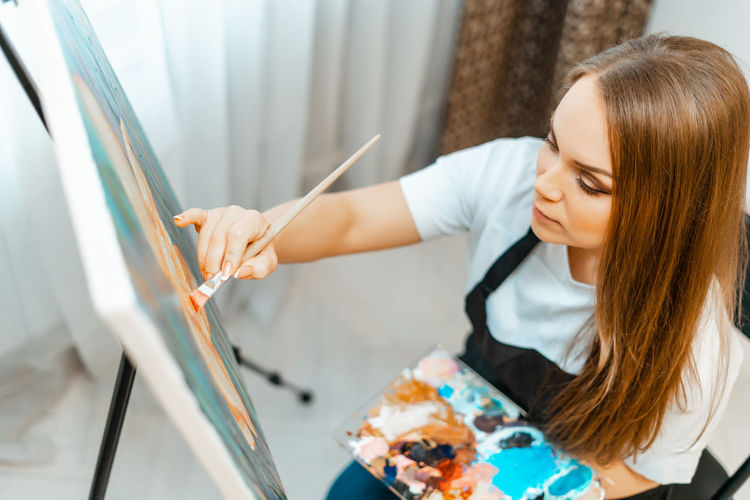 High angle view of woman painting on canvas at home