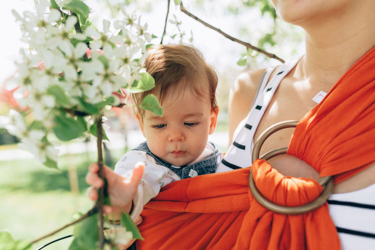 Beautiful adorable baby with her mother at the spring flowers blossom background. Mom and daughter love Child Childhood Real People Baby Innocence Young Front View Cute Lifestyles Babyhood Toddler  Flower Looking Holding Plant Portrait Adorable Boy Girl Sling Baby Sling Baby Holding Spring Springtime Love