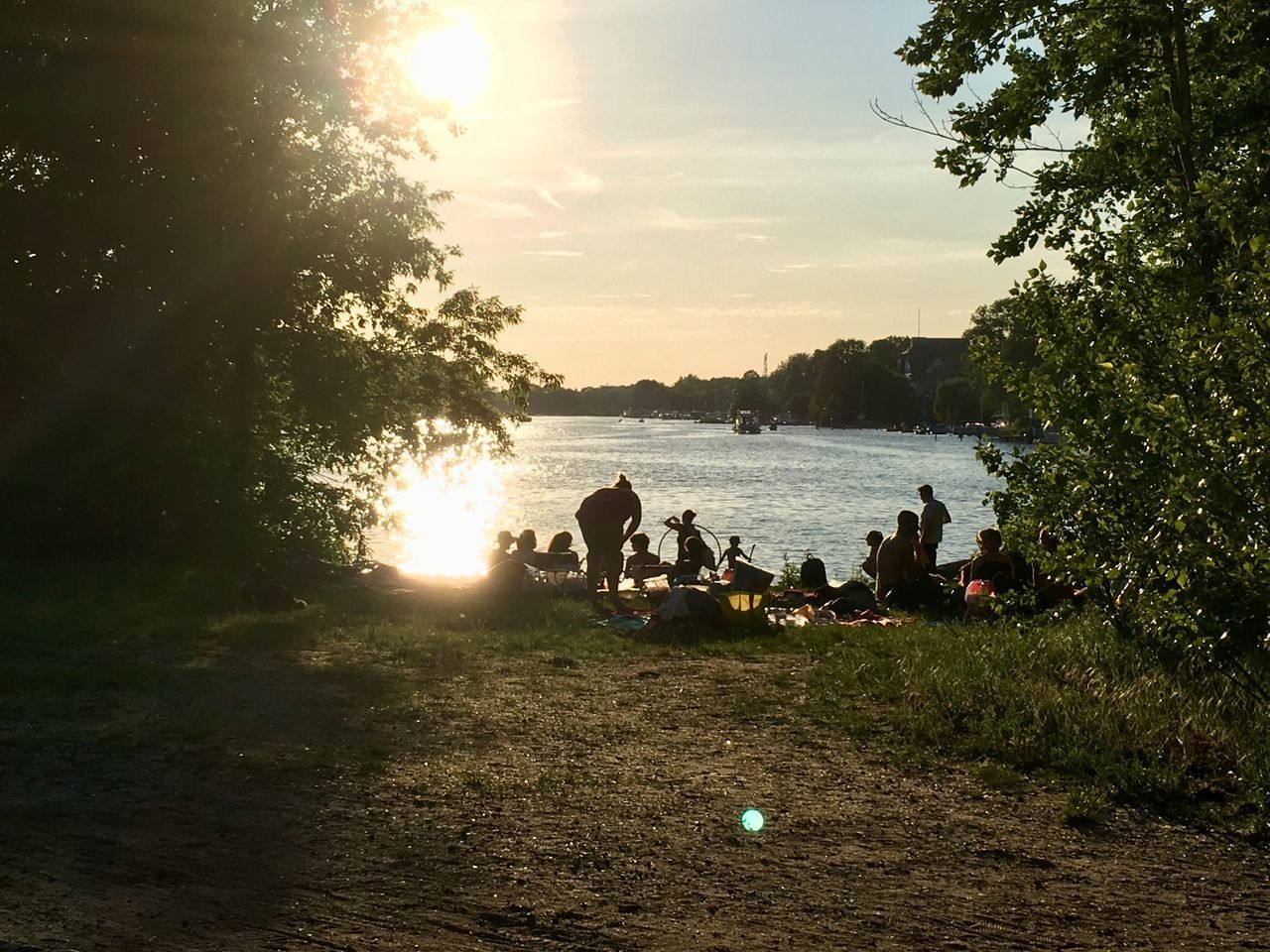 PEOPLE SITTING ON SHORE AGAINST SKY DURING SUNSET