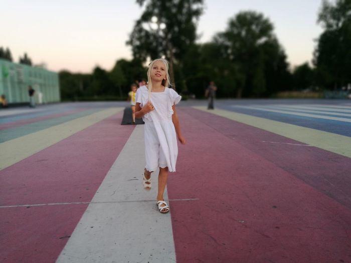 Thoughtful girl walking on running track at stadium during sunset