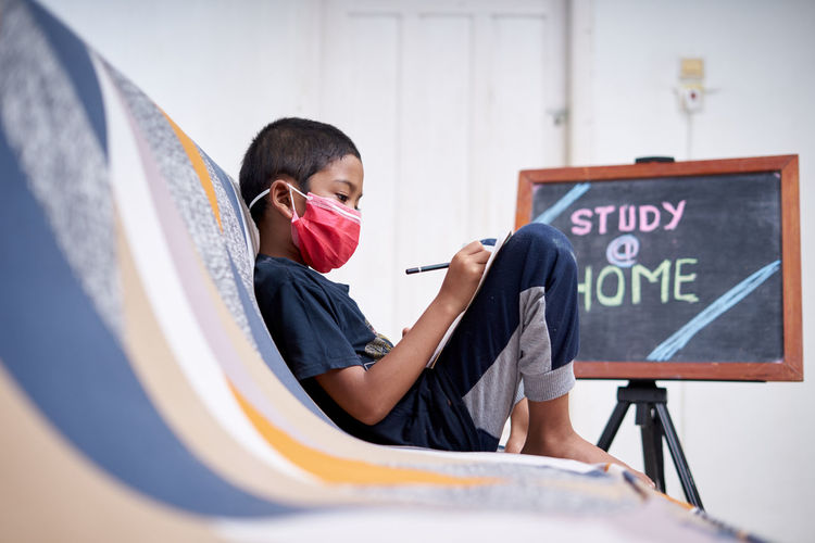 Side view portrait of boy sitting with text