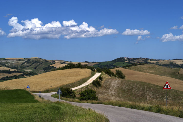 Scenic view of road by land against sky