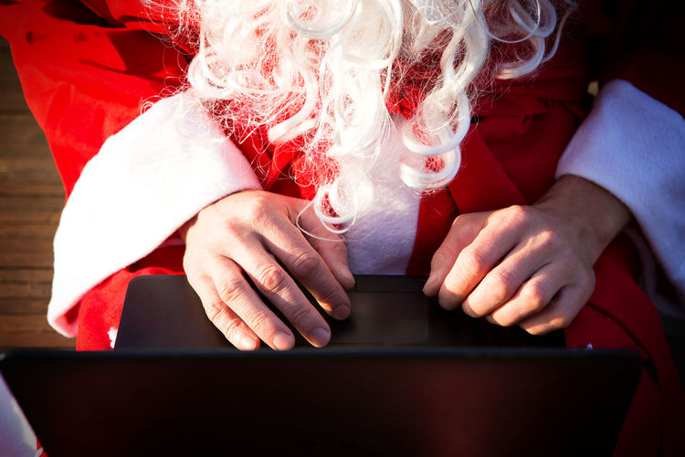 Midsection of man wearing santa claus costume using laptop