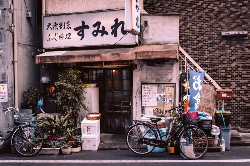 Building Exterior Built Structure Architecture Transportation City Text Bicycle Street Day Sign Entrance Building