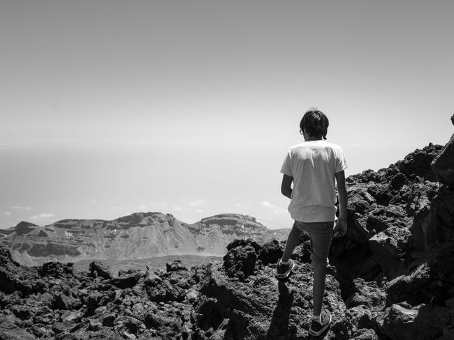 Monochrome Photography Rear View Standing Leisure Activity Men Copy Space Getting Away From It All Scenics Looking At View Tranquil Scene Clear Sky Mountain Tranquility Remote Beauty In Nature Casual Clothing Water Solitude Nature Escapism Non-urban Scene