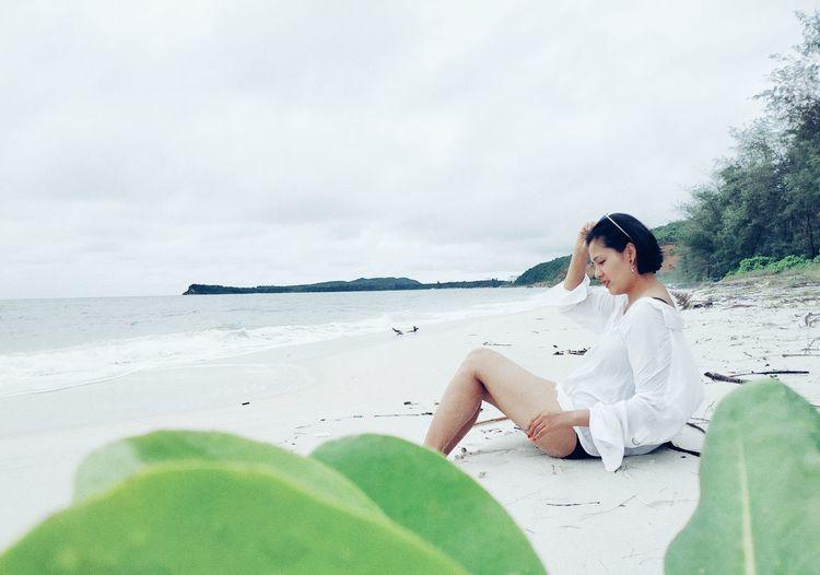 Woman Sitting At Beach Against Sky