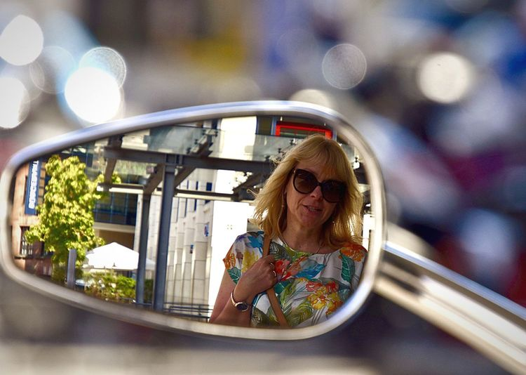 Mature woman reflecting on side-view mirror of motorcycle