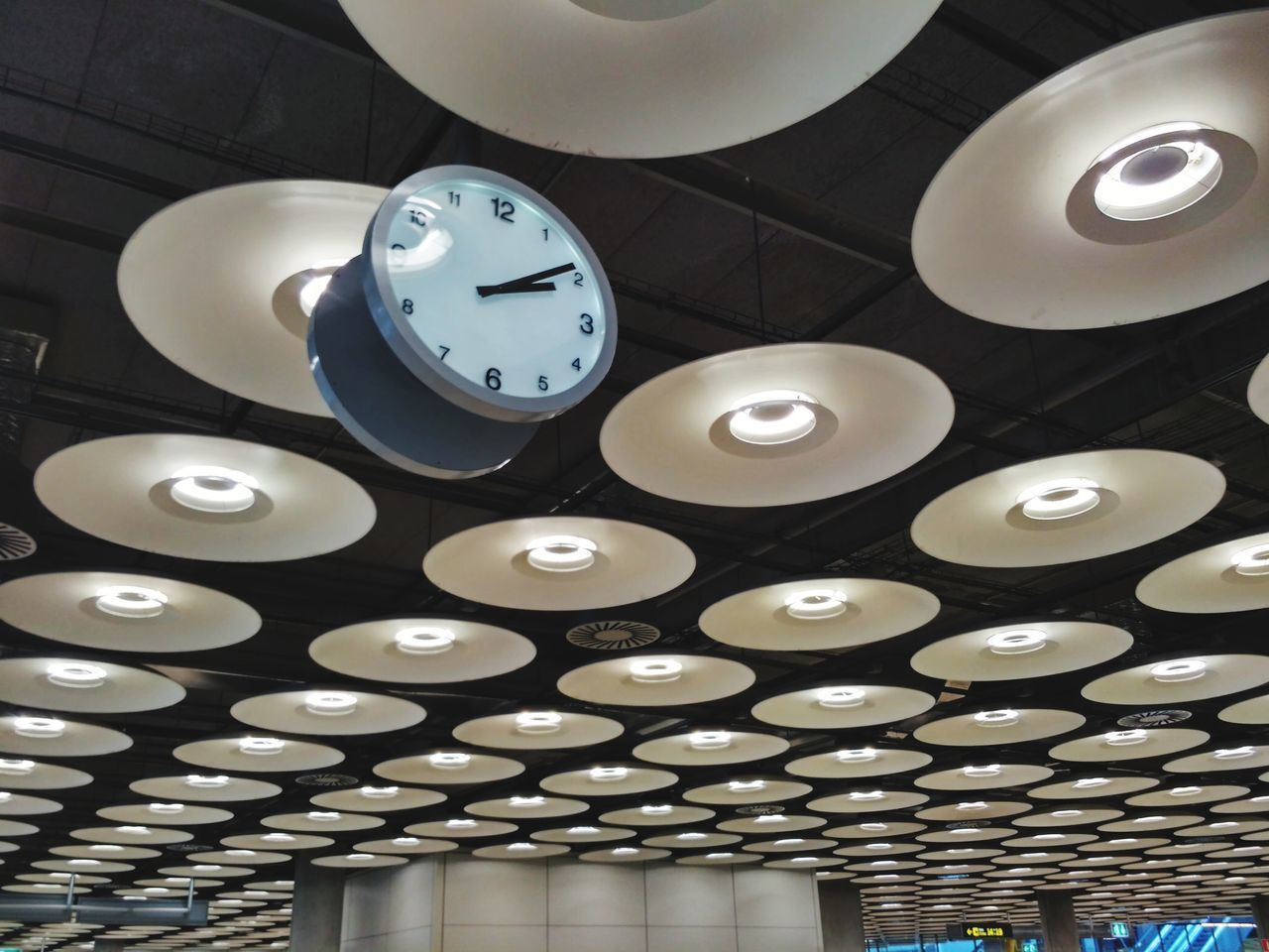 indoors, clock, time, lighting equipment, illuminated, circle, ceiling, low angle view, shape, geometric shape, hanging, no people, light, design, electricity, built structure, pendant light, architecture, electric light, wall - building feature, clock face, wall clock, electric lamp