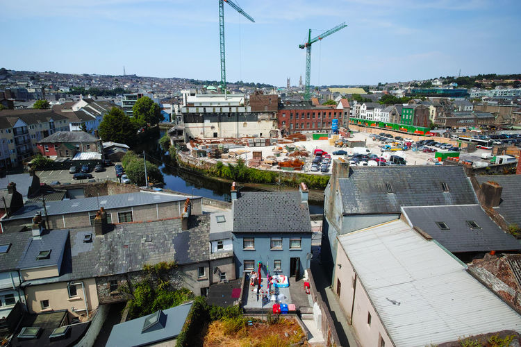 It is hard to imagine that Ireland is suffering housing crisis after a great recession in 2008, where the household value dropped many can not either find a place to rent or being afford this photography there is a lady enjoying her afternoon sunbath surrounded by the existing building and new construction site. Cork Ireland The Architect - 2018 EyeEm Awards Building Built Structure High Angle View House Housing Crisis Incidental People