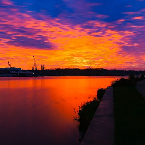 Scenic view of river against romantic sky at sunset