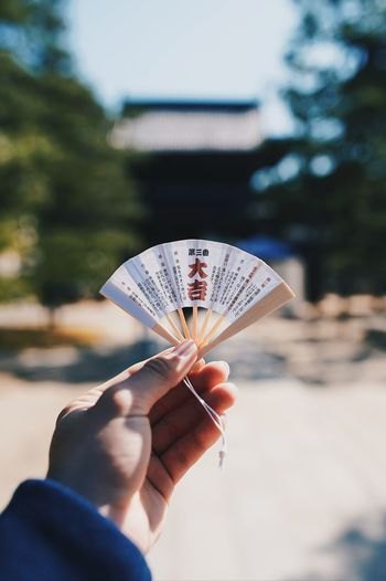 Close-up of hand holding small folding fan