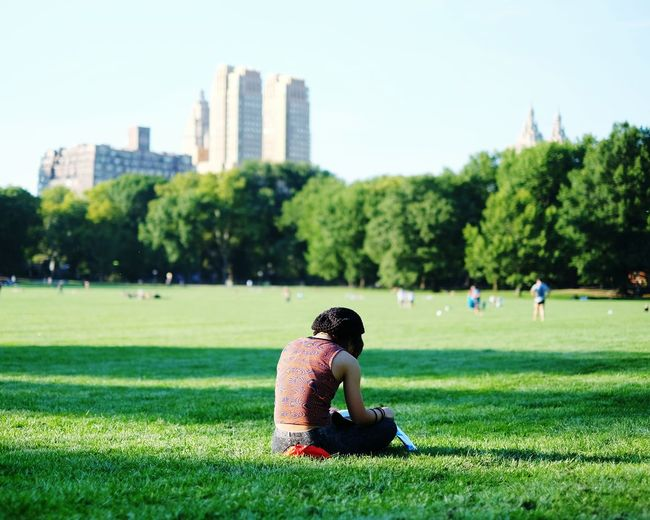 Rear View Of Woman Relaxing In Central Park Against Sky In City