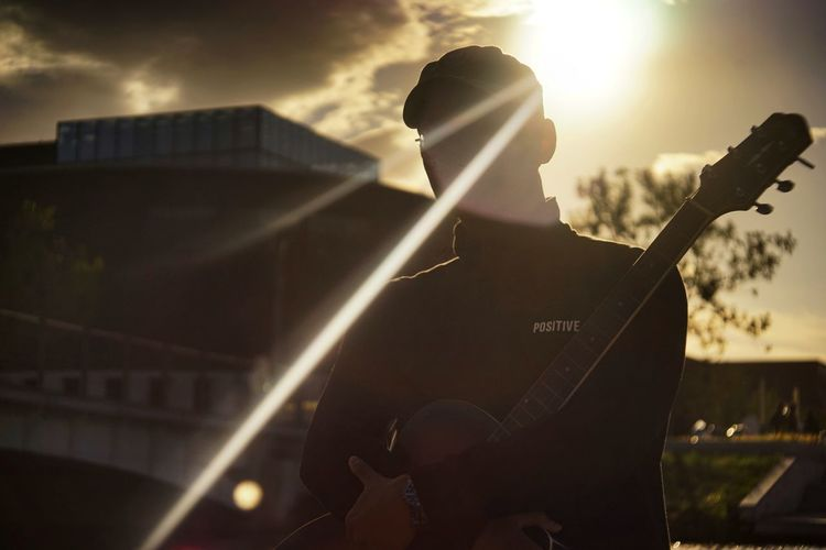 Architecture Artist Arts Culture And Entertainment Guitar Hat Leisure Activity Lens Flare Lifestyles Men Music Musical Instrument Musician Nature One Person Outdoors Performance Playing Plucking An Instrument Real People Rock Music String Instrument Sunlight