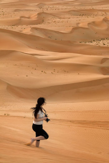 Side view of woman with camera walking in desert