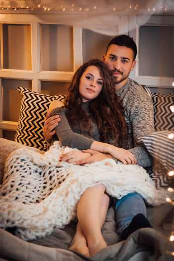 Portrait Of Young Couple Sitting On Bed At Home