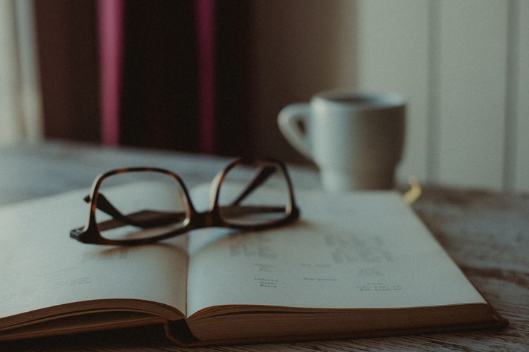 Grain Film Grain Film Education Learning Selective Focus No People Still Life Publication Book Table Glasses Eyeglasses  Indoors  Mug Cup Paper Personal Accessory Coffee Cup Open Focus On Foreground Coffee Coffee Time Close-up Drink Page Communication